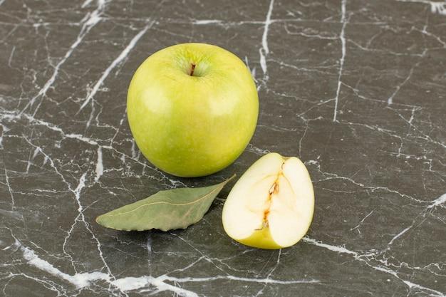 Verse biologische appels. geheel en in plakjes gesneden op grijs.