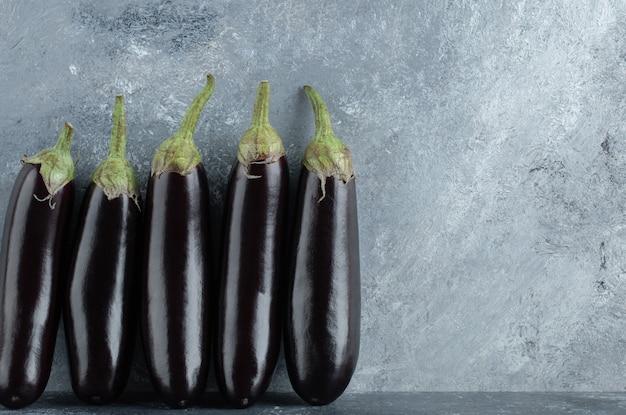 Verse biologische aubergine in rij op grijze achtergrond.