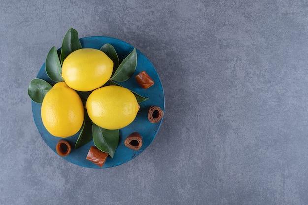 Verse biologische citroenen en bladeren op blauw bord.