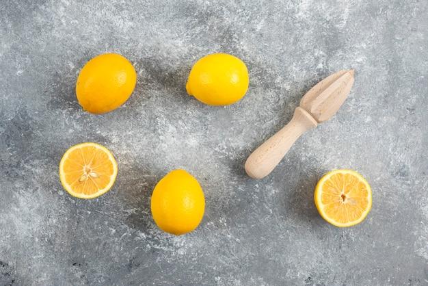 Verse biologische citroenen en pers op grijze ondergrond.