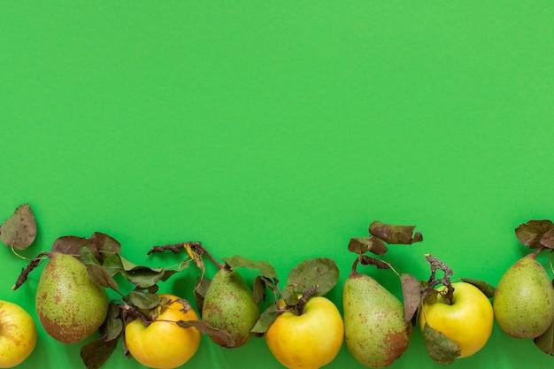 Verse biologische gele appels en groene peren met bladeren op een groene muur