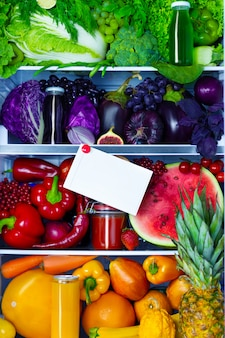 Verse biologische gezonde rauwe antioxidant violet, rood, groen, oranje en geel voedsel, groenten, fruit en sappen in veganistisch vegetarisch opende een volledige koelkast met vitamines met ruimte voor tekst. gezond eten.