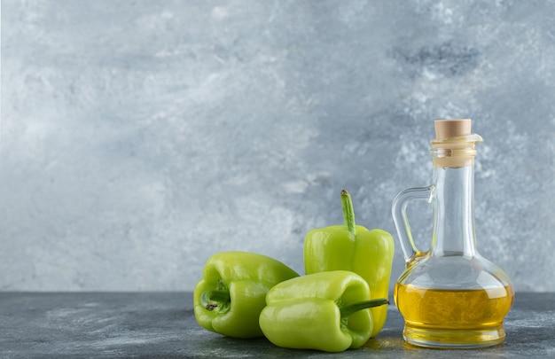 Verse biologische groene paprika's met fles olie over grijze achtergrond.