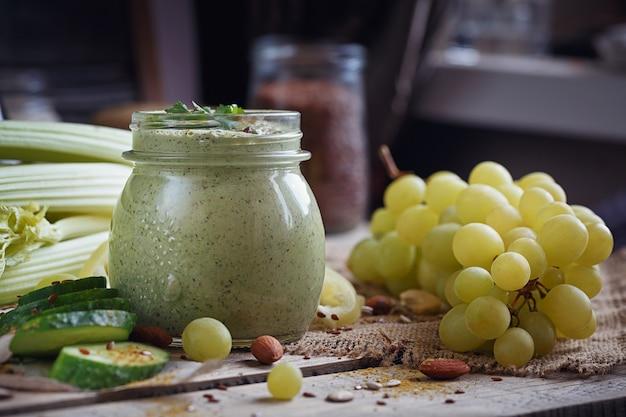 Verse biologische groene smoothie met komkommer, peterselie, druiven en selderij op rustieke houten achtergrond