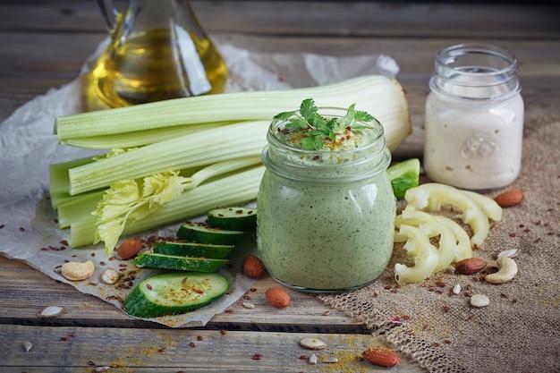 Verse biologische groene smoothie met komkommer, peterselie en selderij op rustieke houten achtergrond