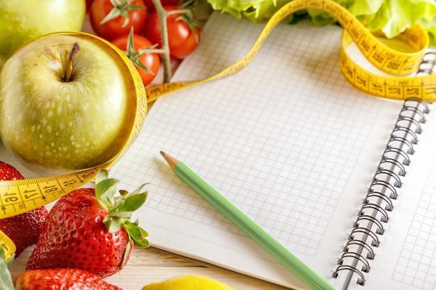 Verse biologische groenten en fruit, lege notitieblok openen en pen op houten