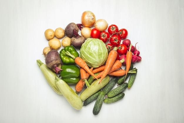 Verse biologische groenten op een witte houten oppervlak. concept van het kopen van boerderij groenten, zorg voor gezondheid, oogst. cirkelvorm. landelijke stijl, farm fair. plat lag, bovenaanzicht