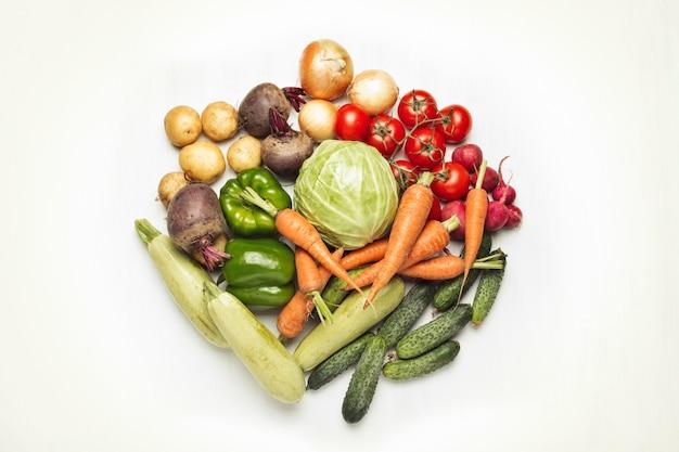 Verse biologische groenten op een witte ondergrond. concept van het kopen van boerderij groenten, zorg voor gezondheid, oogst. cirkelvorm. landelijke stijl, farm fair. plat lag, bovenaanzicht