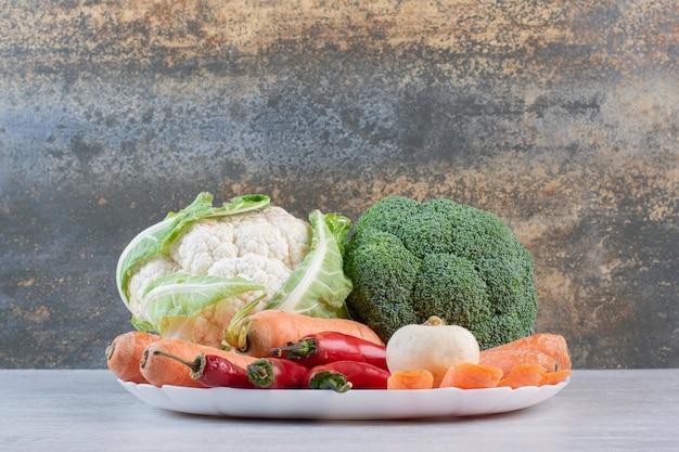 Verse biologische groenten op witte plaat. hoge kwaliteit foto