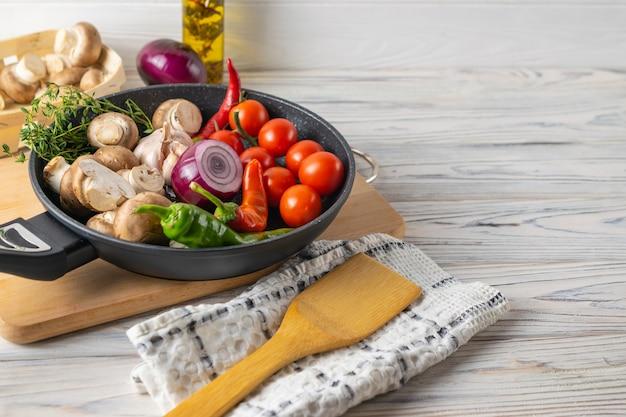 Verse biologische groenten, tomaten, champignons, paprika en tijm in een koekenpan
