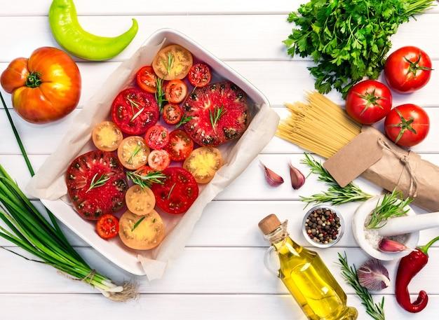 Verse biologische ingrediënten, pastaspaghetti van italiaanse recepten. tomaten met rozemarijn in keramiek.