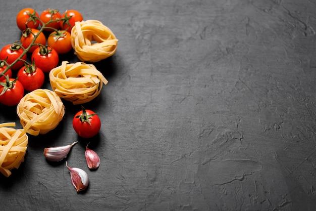Verse biologische ingrediënten van italiaanse recepten. pasta, tomaten, knoflook. gezond voedselconcept.