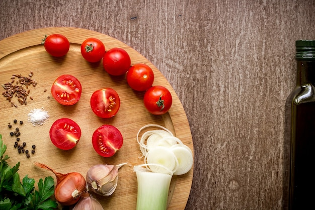 Verse biologische ingrediënten voor het maken van salades: spinazie, tomaten, spruiten, basilicum, olijfolie op rustieke achtergrond, bovenaanzicht. plat leggen met plaats voor tekst. veganistisch en gezond voedingsconcept