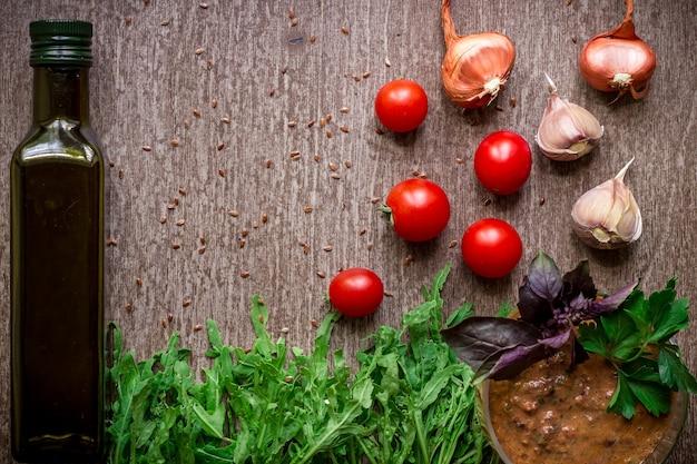 Verse biologische ingrediënten voor het maken van saus spinazie tomaten spruiten basilicum olijfolie op rustieke achtergr...