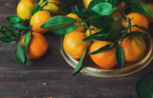 Verse biologische mandarijnen met bladeren op rustieke houten oppervlak.
