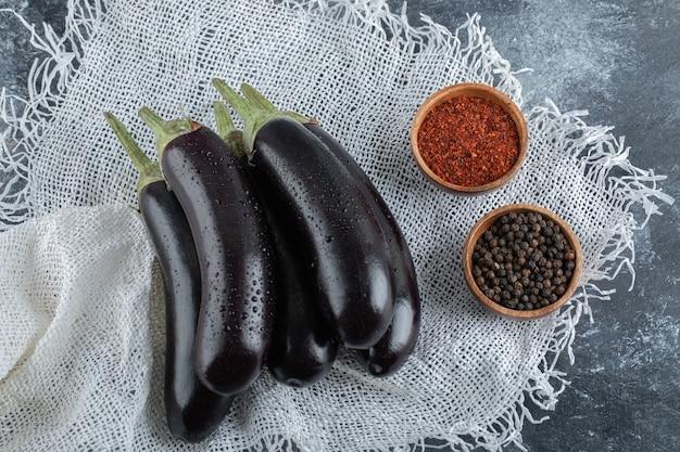Verse biologische paarse aubergines met kruiden, rode en zwarte peper op zak.