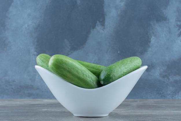 Verse biologische rijpe komkommers in witte kom over grijze achtergrond.