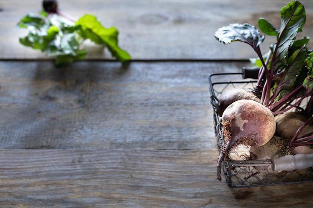 Verse biologische rode bieten met bladeren in een rieten mand op een houten tafel. natuurlijke biologische groenten. herfst oogst. rustiek. kopieer ruimte