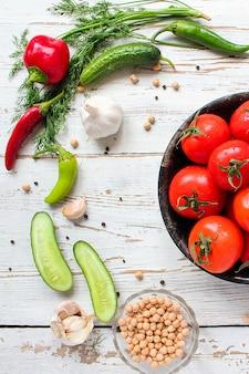 Verse biologische rode tomaten in zwarte plaat op witte houten tafel met groene en rode en chili pepers, groene pepers, zwarte peperkorrels, zout, close-up, gezond concept