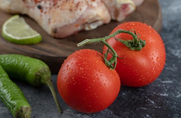 Verse biologische tomaten en paprika's met rauwe kippenpoten
