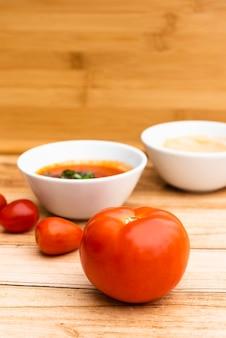 Verse biologische tomaten en saus op houten tafel
