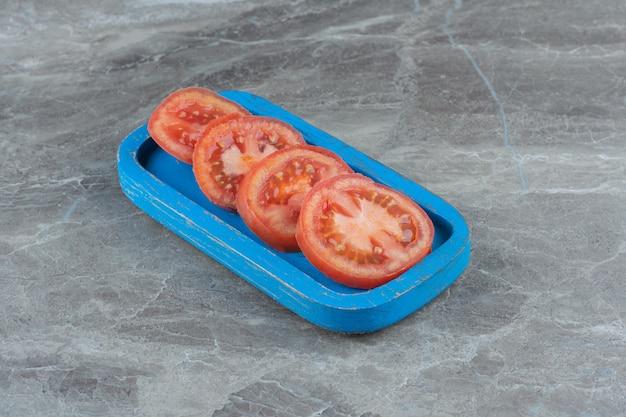 Verse biologische tomatenschijfjes op blauwe houten plank