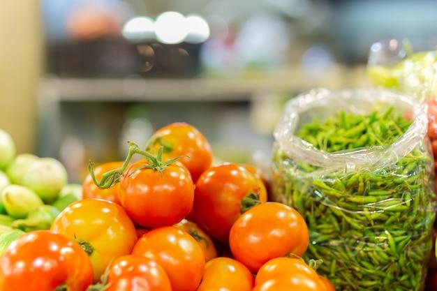 Verse biologische tomatenstapel en groene chili in oogstwinkel