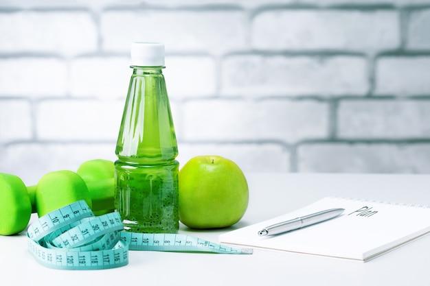 Verse biologische voeding, sportuitrusting, meetlint en open blanco notitieboekje op lichtgrijze achtergrond met kopieerruimte. gezonde voeding en gezond leven concept.