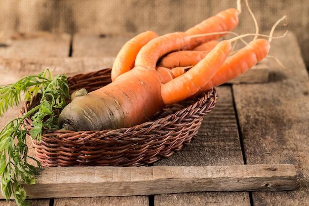 Verse biologische wortelen in een mand op houten oppervlak