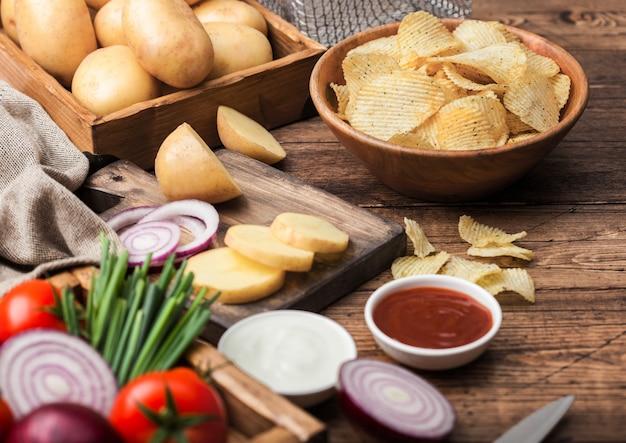 Verse biologische zelfgemaakte chips chips in houten kom met zure room en rode uien en kruiden