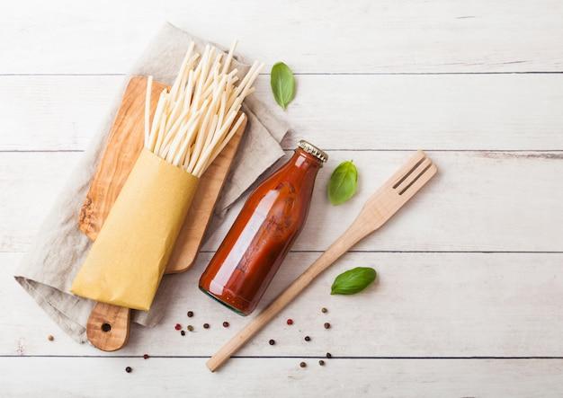 Verse biologische zelfgemaakte spaghetti pasta met fles tomatensaus en houten spatel en basilicum blad op houten bord.