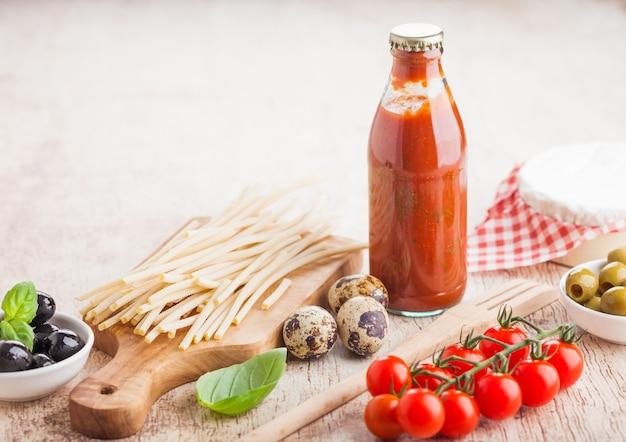 Verse biologische zelfgemaakte spaghetti pasta met kwarteleitjes en verse tomaten met fles tomatensaus en houten spatel en basilicum. klassiek italiaans eten