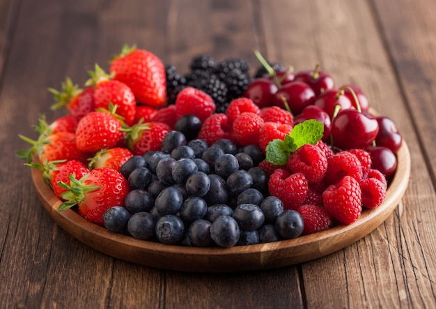 Verse biologische zomerbessen mix in ronde houten dienblad op lichte houten tafel achtergrond. frambozen, aardbeien, bosbessen, bramen en kersen. bovenaanzicht