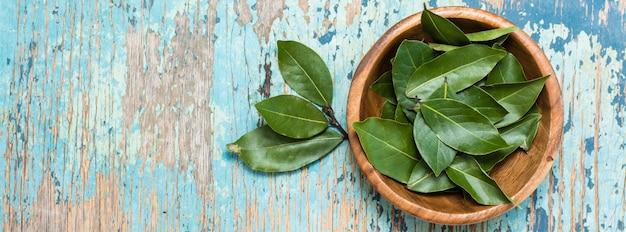 Verse bladeren van laurierbladeren in een kom en ernaast op een houten rustieke tafel. copyspace. webbanner. copyspace