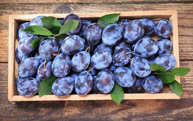 Verse blauwe pruimen met bladeren in houten kist, bovenaanzicht