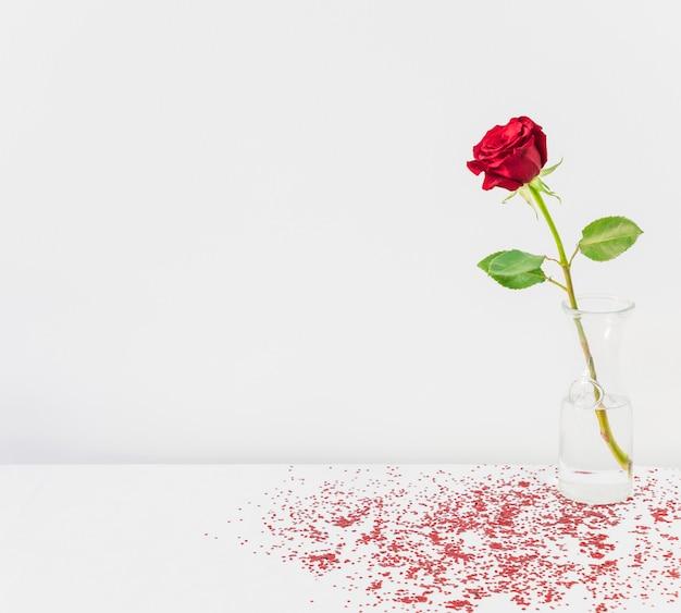 Verse bloei in vaas tussen confetti op tafel