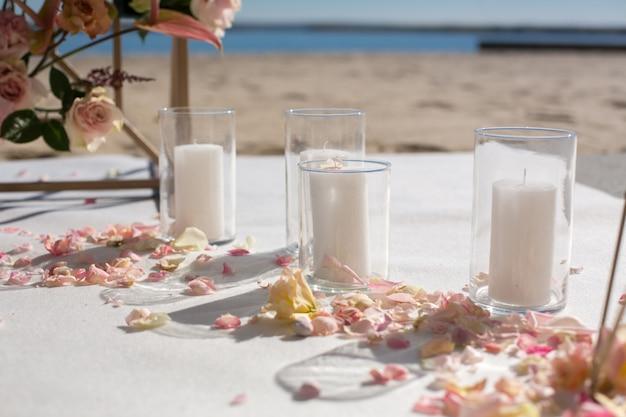 Verse bloembloemblaadjes liggen op de grond naast een versierde huwelijksboog en witte kaarsen