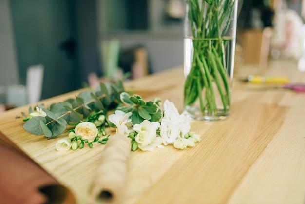 Verse bloemen in vaas tegen decoratiegereedschap en materialen. bloemenbedrijf, bloemistconcept