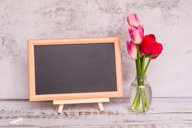Verse bloemen op stengels in vaas en schoolbord