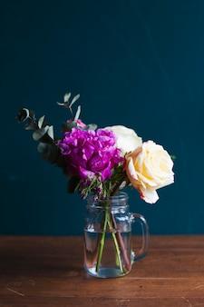 Verse bloemenregeling in een vaas op houten lijst