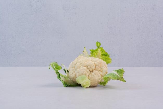 Verse bloemkool met bladeren op witte tafel.