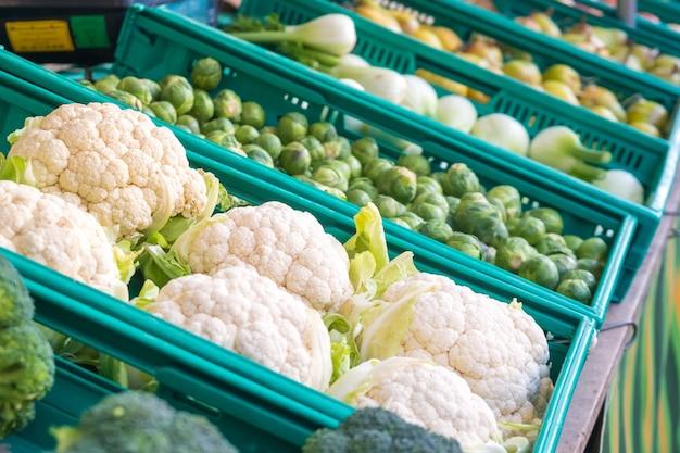 Verse bloemkool met witte kroppen en groene bladeren op wekelijkse markt.