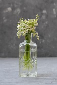 Verse boeketten van lelietje-van-dalen in glazen vazen op grijs