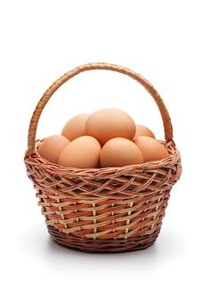 Verse boerderij eieren in rieten mand geïsoleerd op witte ruimte