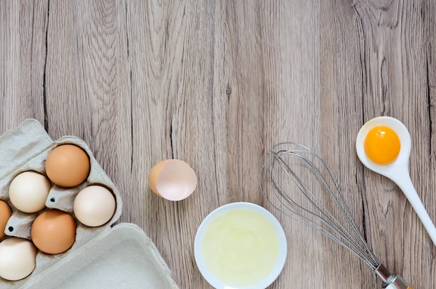 Verse boerderij eieren op een houten rustieke achtergrond. gescheiden eiwit en dooiers, gebroken eierschalen. klop eieren met garde. Premium Foto
