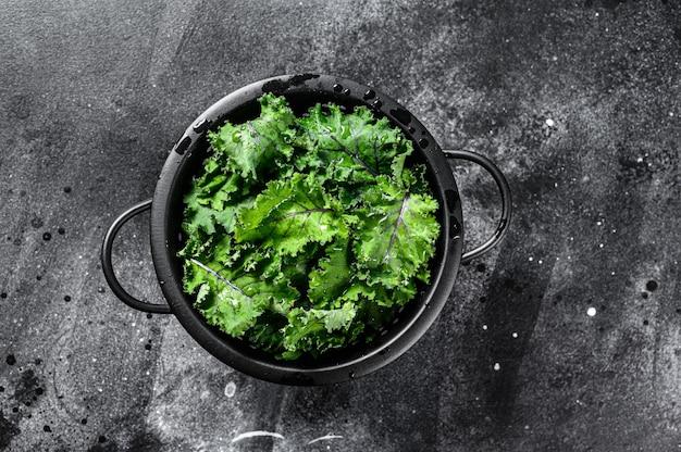 Verse boerenkoolsalade in een vergiet. vegetarisch eten. zwarte achtergrond. bovenaanzicht.