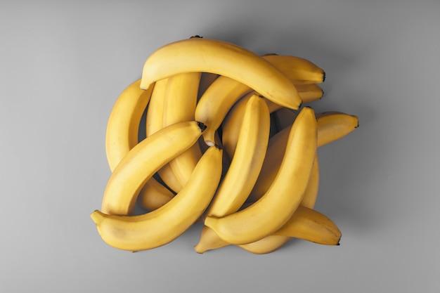 Verse bos gele bananen geïsoleerd op een grijze achtergrond.