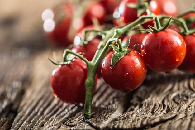 Verse bos rijpe tomaten op oude eiken tafel.