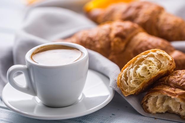 Verse boterachtige croissants met koffie. zoet ochtendontbijtconcept.