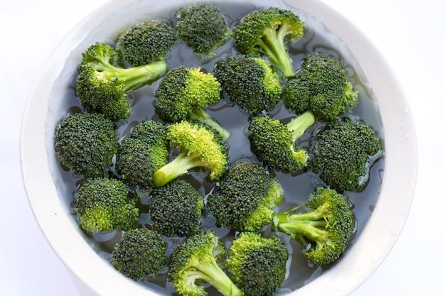 Verse broccoli gedrenkt in een witte kom met water